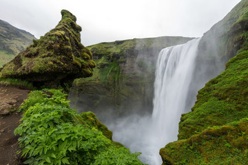 Skogafoss waterfall among green cliffs, South Iceland