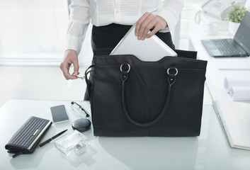 Businesswoman putting essential things into her handbag