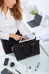 Young stylish businesswoman using digital tablet in office