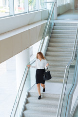 Young businesswoman walking downstairs in office building