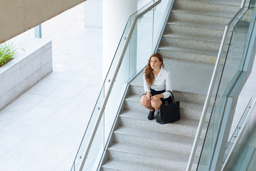 Female office worker sitting on steps and thinking