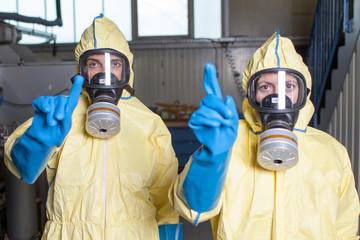 Zwei Helfer in Schutzanzuegen warnen vor Ebola