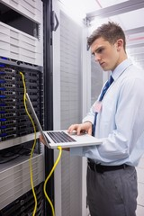 Technician using laptop while analysing server