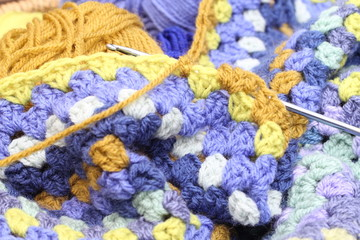 Crocheting an afghan blanket, shades og blue and brown