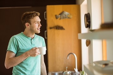 Young man smiling and holding coffee