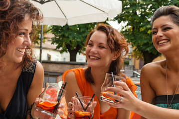 Happy young girl friends having fun in a bar drinking cocktail.