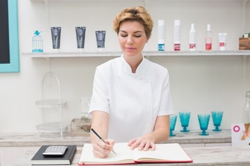 Pretty beautician writing in appointment book