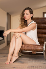 Intimate portrait of beautiful woman on armchair.