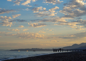 Sunrise on the summer beach with blue hills on the horizon