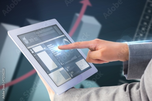 canvas print picture Composite image of businesswoman using a tablet pc