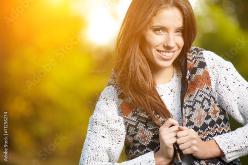 canvas print picture Beautiful elegant woman standing in a park in autumn