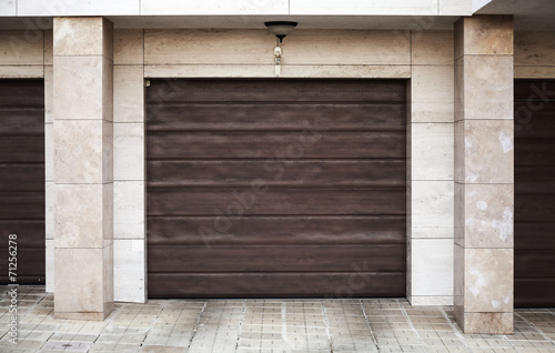 Brown garage gate in living house wall