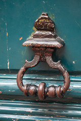 Old rusted knocker on green wooden door in Paris, France
