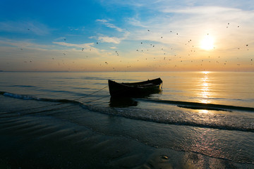 Fisher boat on beach on the sea at sunrise