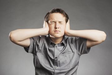 Porträt Teenager Junge: Hält sich Ohren zu Augen geschlossen