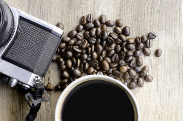 cup of coffee with beans and camera on wood table  from above