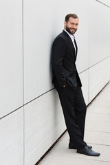mann im schwarzen anzug lehnt an der wand