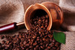 Coffee beans in ibrik on sacking background closeup