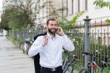 lächelnder mann telefoniert in der stadt