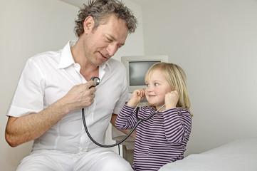 Kleines Mädchen hört mit Stethoskop den Herzschlag eines Arztes
