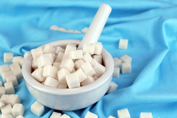 Refined sugar in mortar on color fabric background