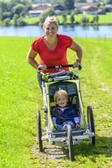 Mama joggt  mit Sohn im Buggy