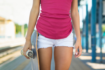 Close up of teenager holding skateboard.