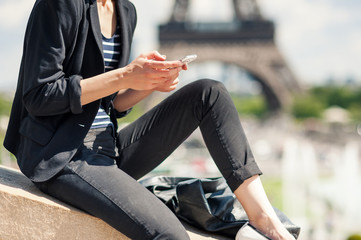 Deteail of young woman using mobile phone in front of the Eiffel