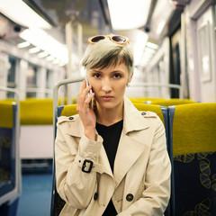 Young woman talking at the phone inside metro subway. Paris, Fra