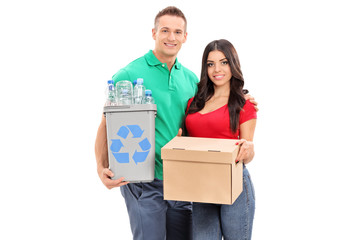 Young couple holding recycle bin and a box