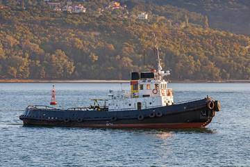 Black tug is underway on Black sea, Varna harbor, Bulgaria