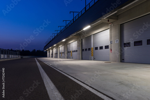 Poster Garages in race circuit. Night time.