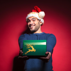 Handsome young santa giving you a green gift