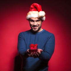 Attractive young santa giving you a small red gift