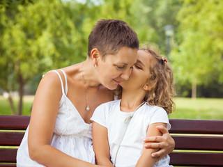 Cute little girl giving her mother a kiss.