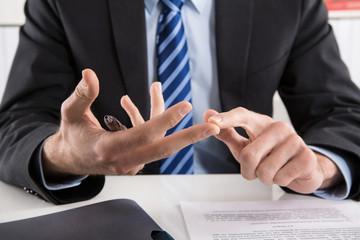 Business Mann zählt Vorteile und Nachteile an den Fingern ab