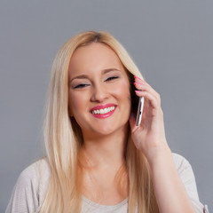 Beautiful young woman talking on the phone and smiling