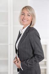 Elegante lachende Frau in Kostüm mit Blazer: Management