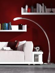 Weißes Sofa vor roter Wand mit Bücherregalen