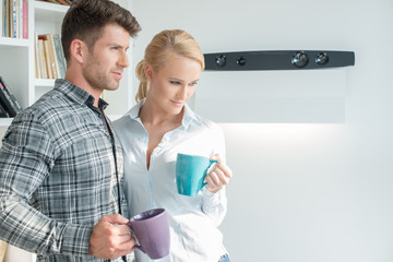 Young couple standing drinking coffee