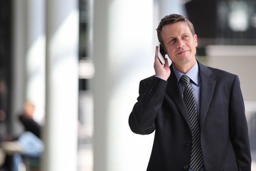 smiling businessman talking on the phone during a business trip