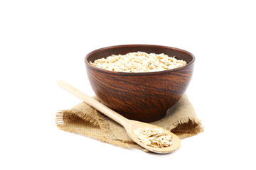 Oatmeal flakes in wooden bowl on white background. Healthy food.