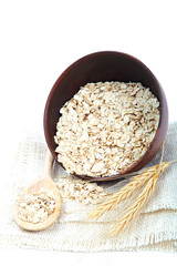 Oatmeal flakes in bowl on white background. Healthy food.