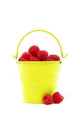 Raspberries in a bucket on a white background.