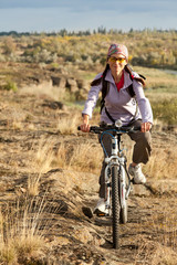 Adult woman pedaling on a mountain bike on off-road