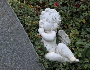Engel liegt neben Grabstein