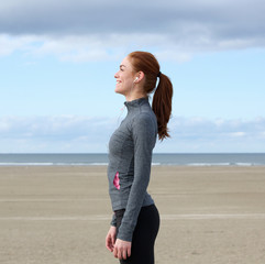 Smiling woman in sports outfit standing outdoors