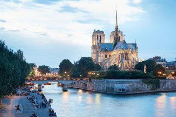 Notre Dame de Paris at dusk, people on docks