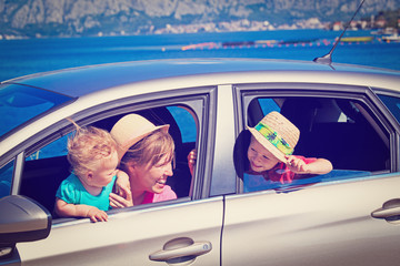 mother with kids travel by car at the sea