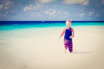 little boy running on sand beach